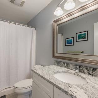 ニューヨークの中サイズのトランジショナルスタイルのおしゃれなバスルーム (浴槽なし) (シェーカースタイル扉のキャビネット、白いキャビネット、アルコーブ型浴槽、シャワー付き浴槽、分離型トイレ、グレーの壁、ライムストーンの床、アンダーカウンター洗面器、珪岩の洗面台、ベージュの床、シャワーカーテン) の写真