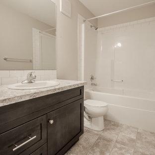 Foto de cuarto de baño principal, tradicional renovado, con armarios estilo shaker, puertas de armario de madera en tonos medios, bañera empotrada, combinación de ducha y bañera, sanitario de dos piezas, baldosas y/o azulejos blancos, baldosas y/o azulejos de cemento, paredes grises, suelo de linóleo, lavabo encastrado y encimera de laminado