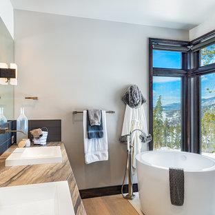 Foto de cuarto de baño principal, rural, con bañera japonesa, baldosas y/o azulejos grises, paredes grises, suelo de madera clara, lavabo sobreencimera y encimeras multicolor