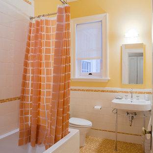 ニューヨークのトラディショナルスタイルのおしゃれな浴室 (コンソール型シンク、アルコーブ型浴槽、シャワー付き浴槽、オレンジのタイル、黄色い壁、モザイクタイル、オレンジの床) の写真