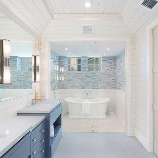 Esempio di una stanza da bagno stile marino con ante lisce, ante blu, vasca freestanding, piastrelle blu, piastrelle a listelli, pareti bianche, lavabo sottopiano, pavimento grigio e top bianco