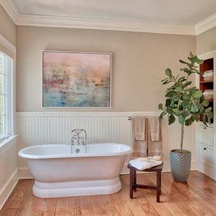 Inspiration for a timeless medium tone wood floor and brown floor freestanding bathtub remodel in New York with white cabinets and beige walls