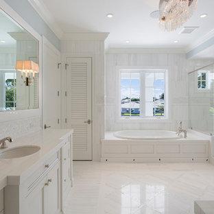 Ispirazione per una stanza da bagno padronale tropicale con ante con riquadro incassato, ante bianche, vasca da incasso, doccia alcova, piastrelle bianche, pareti blu, lavabo sottopiano, pavimento bianco, porta doccia a battente e top bianco
