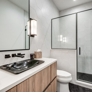 Alcove shower - mid-sized contemporary 3/4 white tile and porcelain tile black floor, single-sink and ceramic tile alcove shower idea in Dallas with flat-panel cabinets, medium tone wood cabinets, a two-piece toilet, a vessel sink, a hinged shower door, white countertops, a floating vanity and white walls