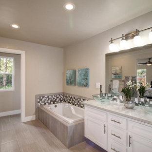 Idées déco pour une salle de bain principale moderne de taille moyenne avec un bain bouillonnant, un mur beige, sol en stratifié, un sol gris, un placard avec porte à panneau encastré, des portes de placard blanches, une douche d'angle, un WC séparé, un carrelage multicolore, carrelage en mosaïque, une vasque, un plan de toilette en quartz modifié, une cabine de douche à porte battante et un plan de toilette beige.