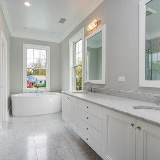 Стильный дизайн: большая главная ванная комната в стиле неоклассика (современная классика) с фасадами с утопленной филенкой, белыми фасадами, отдельно стоящей ванной, душем в нише, раздельным унитазом, серой плиткой, белой плиткой, плиткой из листового камня, серыми стенами, мраморным полом, врезной раковиной, столешницей из талькохлорита, разноцветным полом и душем с распашными дверями - последний тренд