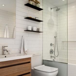 Стильный дизайн: маленькая детская ванная комната в современном стиле с плоскими фасадами, ванной в нише, душем над ванной, унитазом-моноблоком, белой плиткой, белыми стенами, открытым душем, фасадами цвета дерева среднего тона, консольной раковиной и серым полом - последний тренд
