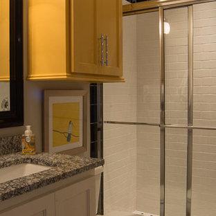 Großes Eklektisches Badezimmer En Suite mit gelben Schränken, Granit-Waschbecken/Waschtisch, Einbaubadewanne, offener Dusche, Toilette mit Aufsatzspülkasten, grauer Wandfarbe, Keramikboden, Schrankfronten mit vertiefter Füllung, schwarz-weißen Fliesen, Keramikfliesen, Unterbauwaschbecken, grauem Boden und Schiebetür-Duschabtrennung in Oklahoma City