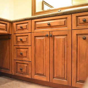 フェニックスの大きいトラディショナルスタイルのおしゃれなマスターバスルーム (レイズドパネル扉のキャビネット、中間色木目調キャビネット、大型浴槽、段差なし、磁器タイル、磁器タイルの床、オーバーカウンターシンク、御影石の洗面台、ベージュの床) の写真