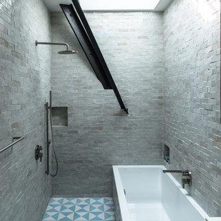 Idéer för mellanstora industriella en-suite badrum, med ett platsbyggt badkar, en öppen dusch, med dusch som är öppen, grå kakel, stenkakel, släta luckor, skåp i mellenmörkt trä, ett nedsänkt handfat, bänkskiva i akrylsten, en vägghängd toalettstol, grå väggar och klinkergolv i keramik
