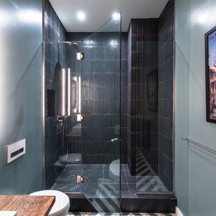 Foto på ett mellanstort industriellt badrum med dusch, med ett fristående handfat, träbänkskiva, en dusch i en alkov, en vägghängd toalettstol, svart kakel, skifferkakel, blå väggar och klinkergolv i keramik