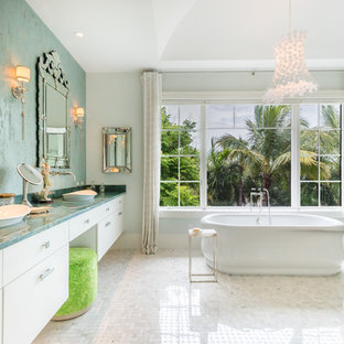 Freestanding bathtub - tropical master white floor freestanding bathtub idea in Miami with flat-panel cabinets, white cabinets, multicolored walls, a vessel sink and blue countertops