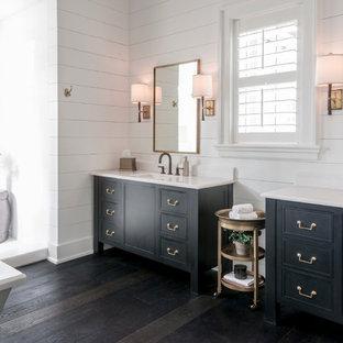 Modelo de cuarto de baño principal, de estilo de casa de campo, grande, con puertas de armario negras, bañera exenta, ducha abierta, paredes blancas, suelo de madera oscura, lavabo bajoencimera, armarios con paneles empotrados y ducha abierta