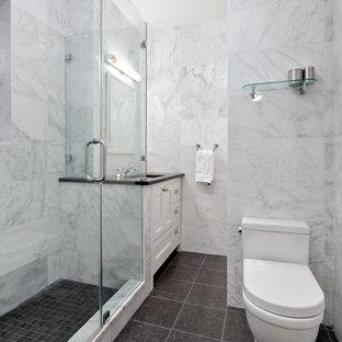 Ispirazione per una piccola stanza da bagno con doccia tradizionale con ante in stile shaker, ante bianche, doccia ad angolo, WC monopezzo, piastrelle nere, piastrelle di vetro, pareti bianche, pavimento in gres porcellanato e top in granito