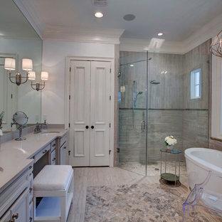 オーランドのトランジショナルスタイルのおしゃれなマスターバスルーム (アンダーカウンター洗面器、置き型浴槽、コーナー設置型シャワー、グレーのタイル、白い壁、白いキャビネット、クオーツストーンの洗面台、石タイル、トラバーチンの床) の写真