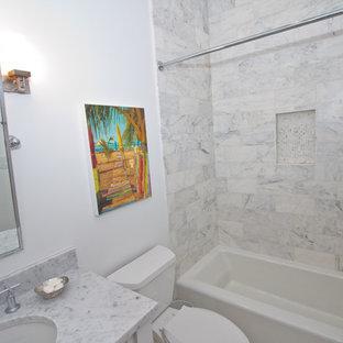 Ispirazione per una stanza da bagno con doccia stile marino di medie dimensioni con ante a filo, ante bianche, vasca ad alcova, vasca/doccia, WC a due pezzi, piastrelle grigie, piastrelle bianche, piastrelle in pietra, pareti rosse, lavabo sottopiano e top in marmo