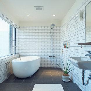 Inredning av ett modernt en-suite badrum, med ett fristående badkar, en kantlös dusch, tunnelbanekakel, vita väggar, ett väggmonterat handfat, grått golv och med dusch som är öppen