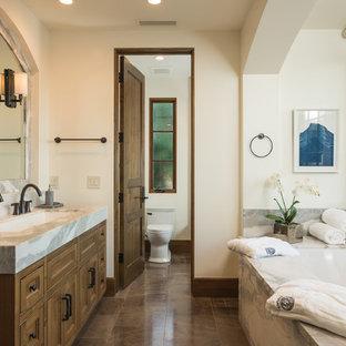 Modelo de cuarto de baño principal, mediterráneo, con armarios con paneles empotrados, puertas de armario de madera oscura, bañera encastrada sin remate, sanitario de una pieza, paredes beige, lavabo de seno grande, encimera de mármol y suelo marrón