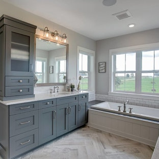 Inspiration for a small farmhouse master white tile medium tone wood floor and beige floor drop-in bathtub remodel in Grand Rapids with shaker cabinets, turquoise cabinets, gray walls, an undermount sink, solid surface countertops and a hinged shower door