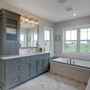 Inredning av ett lantligt litet en-suite badrum, med skåp i shakerstil, turkosa skåp, ett platsbyggt badkar, vit kakel, grå väggar, mellanmörkt trägolv, ett undermonterad handfat, bänkskiva i akrylsten, beiget golv och dusch med gångjärnsdörr