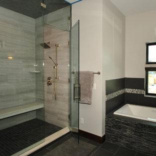 ソルトレイクシティの広いコンテンポラリースタイルのおしゃれなマスターバスルーム (シェーカースタイル扉のキャビネット、グレーのキャビネット、ドロップイン型浴槽、アルコーブ型シャワー、白いタイル、白い壁、スレートの床、オーバーカウンターシンク、珪岩の洗面台、黒い床、開き戸のシャワー) の写真
