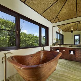 Modelo de cuarto de baño principal, asiático, de tamaño medio, con armarios con paneles empotrados, puertas de armario de madera en tonos medios, bañera exenta, paredes beige, suelo de mármol, lavabo bajoencimera, encimera de mármol, suelo verde y encimeras blancas