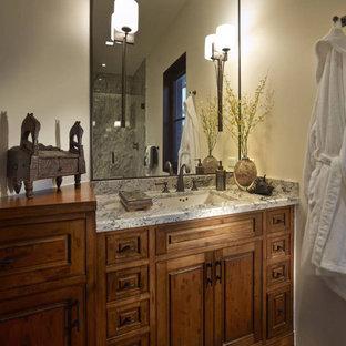 Idee per una piccola stanza da bagno con doccia etnica con ante con bugna sagomata, ante marroni, pareti beige, pavimento in legno massello medio, lavabo sottopiano, top in granito, pavimento marrone e top multicolore