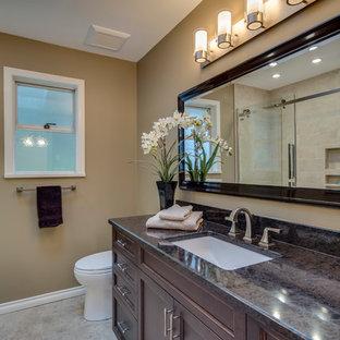 Foto de cuarto de baño infantil, contemporáneo, de tamaño medio, con armarios con paneles empotrados, puertas de armario de madera en tonos medios, ducha empotrada, sanitario de una pieza, baldosas y/o azulejos beige, baldosas y/o azulejos de piedra, paredes marrones, suelo de linóleo, lavabo bajoencimera y encimera de granito