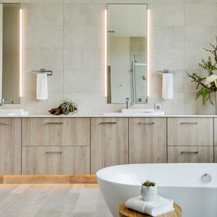 Trendy master beige tile freestanding bathtub photo in Austin with flat-panel cabinets and light wood cabinets