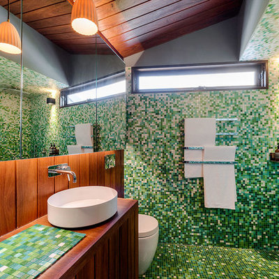 Inspiration for a contemporary green tile and mosaic tile mosaic tile floor bathroom remodel in Melbourne with a one-piece toilet, green walls, a vessel sink, tile countertops and green countertops