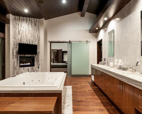 Modernes Badezimmer En Suite Mit Flächenbündigen Schrankfronten,  Hellbraunen Holzschränken, Whirlpool, Grauen Fliesen,