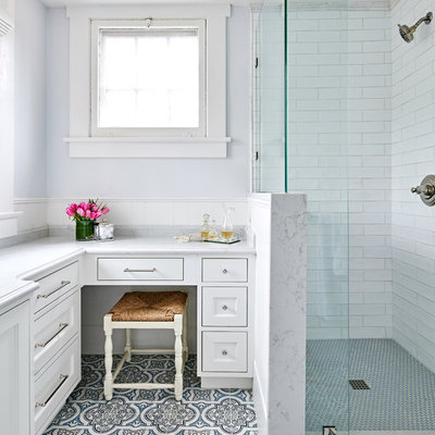 Corner shower - small traditional kids' white tile and ceramic tile marble floor and blue floor corner shower idea in Austin with shaker cabinets, white cabinets, a two-piece toilet, blue walls, an undermount sink, quartz countertops, a hinged shower door and white countertops