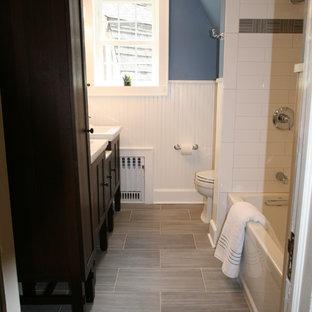 Ejemplo de cuarto de baño principal, de estilo americano, de tamaño medio, con armarios estilo shaker, puertas de armario negras, bañera empotrada, combinación de ducha y bañera, sanitario de dos piezas, paredes azules, suelo de baldosas de porcelana, lavabo bajoencimera y encimera de acrílico