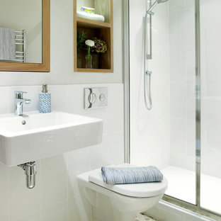 Photo of a small classic bathroom in London with a wall-mounted sink, an alcove shower, a wall mounted toilet, white tiles, ceramic tiles, white walls and pebble tile flooring.