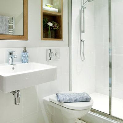 Small transitional white tile and ceramic tile pebble tile floor alcove shower photo in London with a wall-mount sink, a wall-mount toilet and white walls
