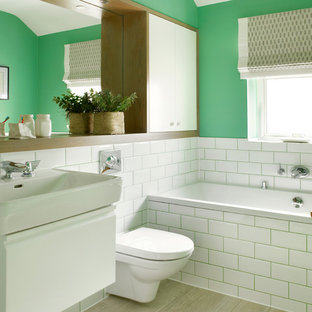 Medium sized classic ensuite bathroom in London with a console sink, flat-panel cabinets, white cabinets, an alcove bath, a wall mounted toilet, white tiles, metro tiles, green walls and porcelain flooring.