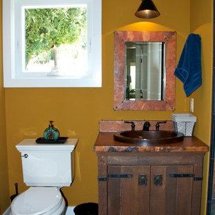 Modelo de cuarto de baño con ducha, de estilo de casa de campo, pequeño, con armarios tipo mueble, puertas de armario de madera en tonos medios, bañera encastrada, combinación de ducha y bañera, sanitario de dos piezas, paredes marrones, suelo de pizarra, lavabo encastrado y encimera de cobre