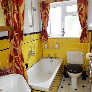 Immagine di una piccola stanza da bagno per bambini moderna con vasca da incasso, vasca/doccia, WC monopezzo, piastrelle gialle, piastrelle in ceramica, pavimento in vinile e lavabo a colonna
