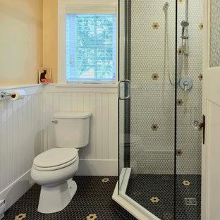 Idee per una stanza da bagno con doccia american style di medie dimensioni con doccia ad angolo, WC a due pezzi, piastrelle multicolore, piastrelle a mosaico, pareti gialle, pavimento con piastrelle a mosaico, pavimento nero, porta doccia a battente e boiserie