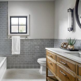 ヒューストンの小さいトランジショナルスタイルのおしゃれな子供用バスルーム (セラミックタイル、グレーの壁、磁器タイルの床、アンダーカウンター洗面器、珪岩の洗面台、白い床、白い洗面カウンター、洗面台1つ、独立型洗面台、中間色木目調キャビネット、アルコーブ型浴槽、グレーのタイル) の写真