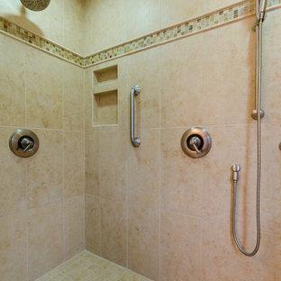 Modelo de cuarto de baño principal, tradicional, de tamaño medio, con armarios con paneles con relieve, puertas de armario de madera oscura, ducha empotrada, sanitario de una pieza, paredes blancas, suelo de linóleo, lavabo bajoencimera y encimera de granito