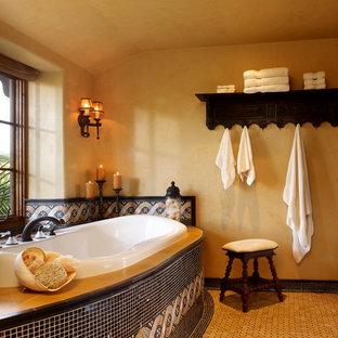 他の地域の大きいトラディショナルスタイルのおしゃれなマスターバスルーム (ライムストーンの洗面台、ドロップイン型浴槽、マルチカラーのタイル、磁器タイル、黄色い壁、磁器タイルの床) の写真