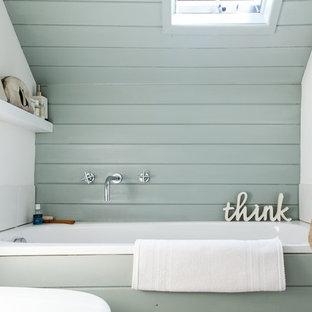 Cette image montre une salle de bain marine avec une baignoire en alcôve et un mur bleu.
