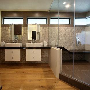 Idee per una grande stanza da bagno padronale minimalista con consolle stile comò, ante bianche, doccia ad angolo, piastrelle multicolore, piastrelle di ciottoli, pareti bianche, parquet chiaro, lavabo a bacinella, top in quarzo composito, pavimento marrone e porta doccia a battente