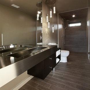 オレンジカウンティの大きいモダンスタイルのおしゃれなバスルーム (浴槽なし) (オープンシェルフ、濃色木目調キャビネット、段差なし、分離型トイレ、グレーのタイル、磁器タイル、ベージュの壁、磁器タイルの床、一体型シンク、ステンレスの洗面台、茶色い床、オープンシャワー) の写真