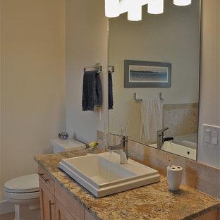 Modelo de cuarto de baño principal, actual, de tamaño medio, con armarios estilo shaker, puertas de armario de madera clara, encimera de granito, baldosas y/o azulejos beige, baldosas y/o azulejos de piedra, sanitario de una pieza, lavabo encastrado, paredes beige y suelo de corcho