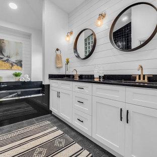 Modelo de cuarto de baño principal y machihembrado, tradicional renovado, grande, machihembrado, con armarios estilo shaker, puertas de armario blancas, bañera encastrada sin remate, paredes blancas, lavabo bajoencimera, suelo gris, encimeras negras y machihembrado