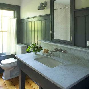 Inredning av ett lantligt badrum, med marmorbänkskiva, ett undermonterad handfat, en toalettstol med separat cisternkåpa, grå väggar och mellanmörkt trägolv