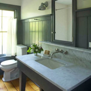 Inspiration for a cottage medium tone wood floor bathroom remodel in New York with marble countertops, an undermount sink, a two-piece toilet and gray walls