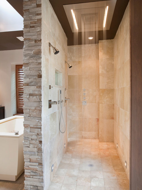 example of a trendy double shower design in dc metro with travertine tile